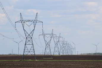 Transmission lines with wind turbines in the background