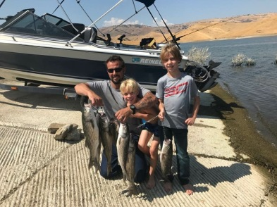 SVP Lineman Dawid Coetzee with his two young sons holding fish in front of their boat on a lake.