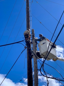 Linemen setting a utility pole