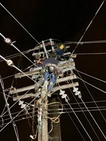 Lineworkers working on distribution lines in a bucket truck at night