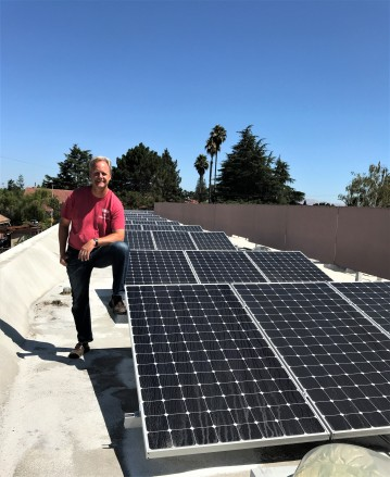 Kurt Ohlfs, Pacific Autism Center for Education executive director standing next to solar panels on their facility's roof